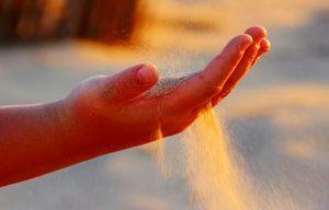 Sand rinnt durch die Finger der Hand und damit lässt sich der Boden feinkruemeliger machen