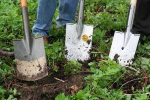 Schneckenzaun aus Metal aufbauen mit Spaten