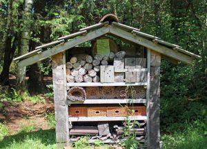 Großes Insektenhotel am Waldrand mit unterschiedlicher Füllung