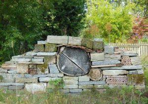 Insektenhotel Insektenhaus aus aufgeschichteten und gestapelten Baumstämmen, Ziegeln und Steinen